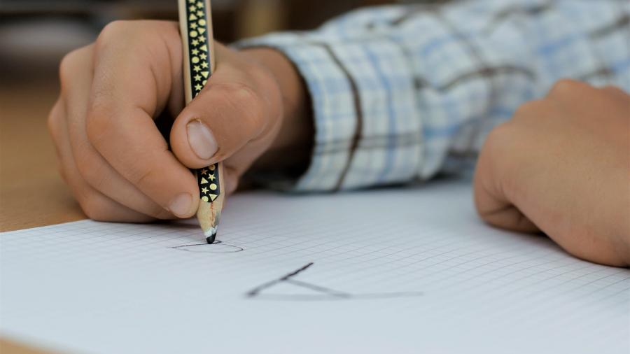 """Egy gyermek keze ceruzát fog és egy négyzetrácsos lapra kis és nagy """"a"""" betűt ír."""